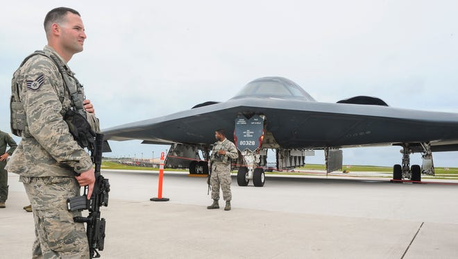 """Sgt. Mathew Meron, front, and Senior Airman James Ballew, with the 509th Security Forces Squadron at Andersen Air Force Base, stand guard near a B-2 """"Spirit"""" bomber aircraft along the base's tarmac on Tuesday, Aug. 16. The bomber is one of three aircraft on deployment to the island and the U.S. Pacific Command area of operations from Whiteman Air Force Base in Missouri, according to an Air Force release."""