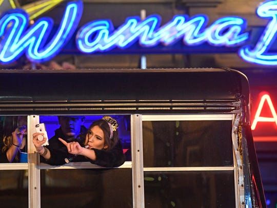 A passenger on a party bus takes a selfie in front