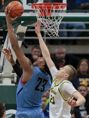 Grand Rapids Christian's Xavier Tillman shoots over Clarkston's Taylor Currie during the Class A boys high school basketball championship at the Breslin Center on Saturday, March 25, 2017.