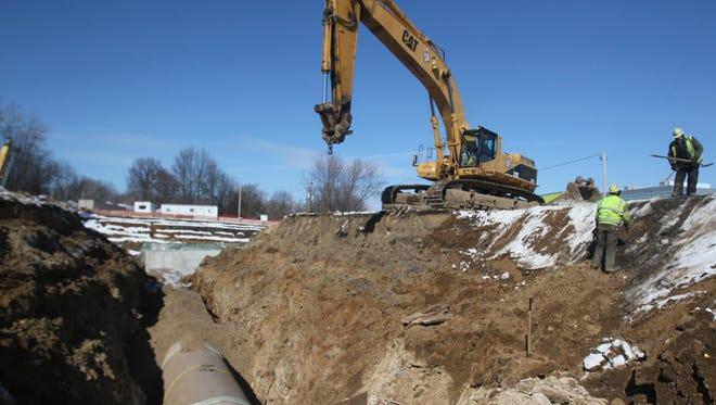 Construction workers from Kenmore Construction Co. talk at Akron's Retention Tank 2 site on Feb. 13 in Akron, Ohio.