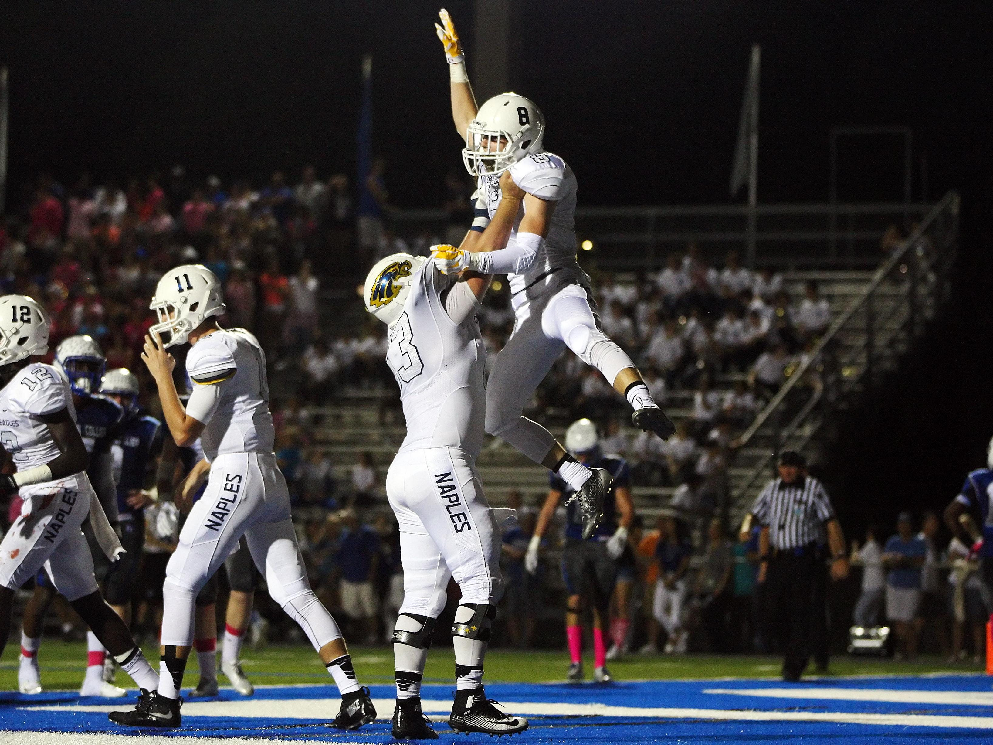 Naples High School's Davis Olson, bottom middle, and Lucas Lee, celebrate Lee's touchdown against Barron Collier on Friday at Barron Collier High School in Naples.