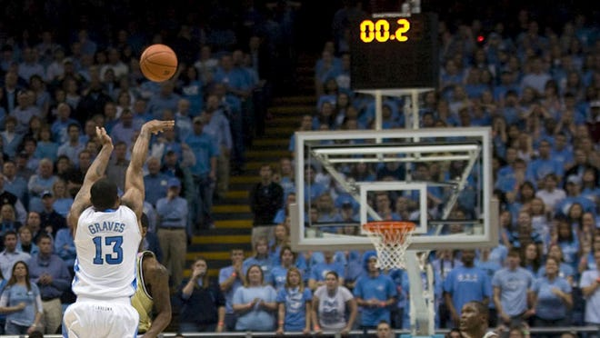 North Carolina's Will Graves (13) shoots with 0.2 seconds left on the backboard mounted shot clock in a 2010 college basketball game. High school coaches in Illinois are being asked if they would support a shot clock.