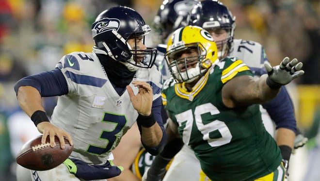 Seattle Seahawks quarterback Russell Wilson (3) scrambles away from Green Bay Packers defensive end Mike Daniels (76) in the fourth quarter.