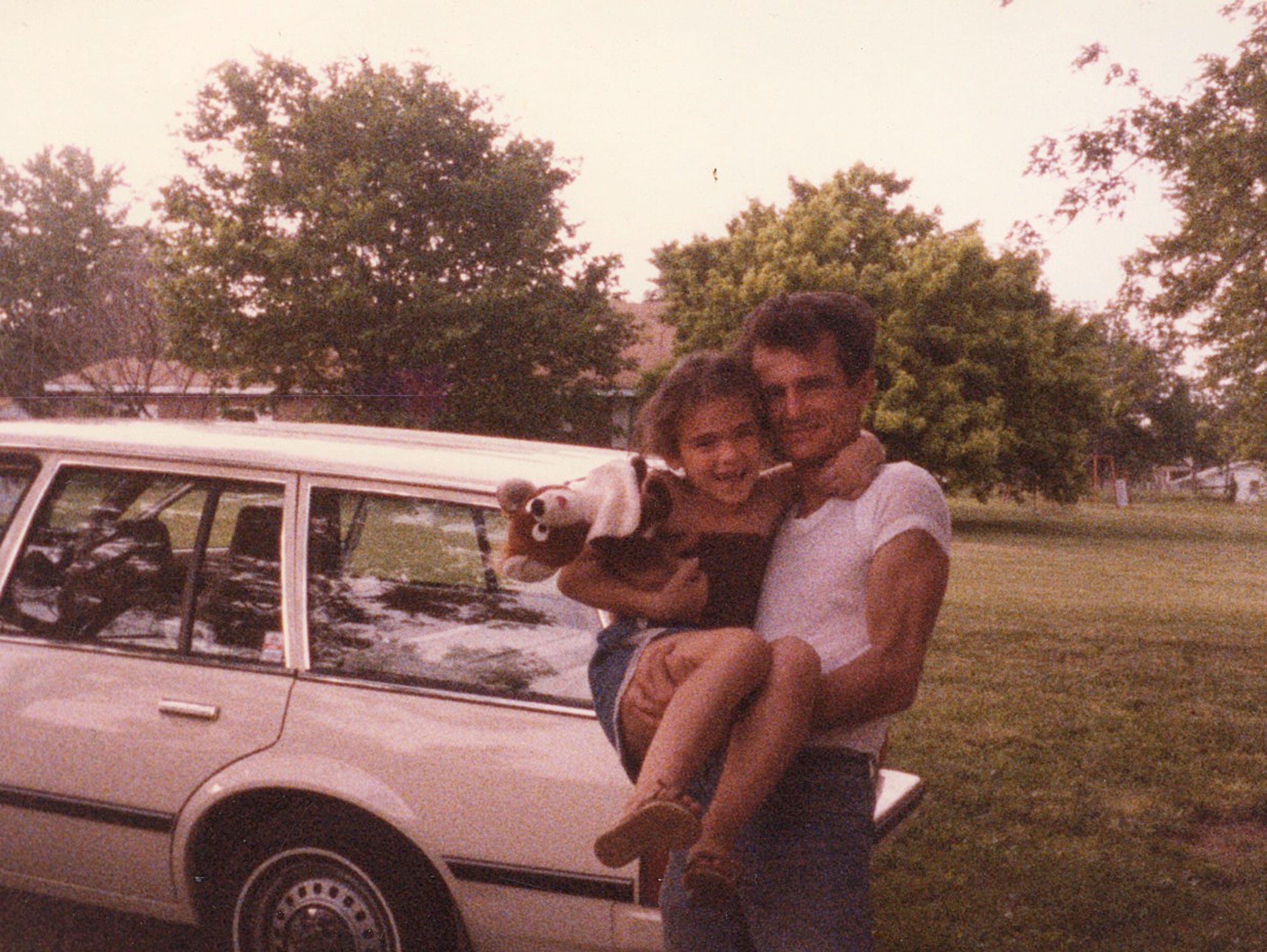 Bob Paillet holds his daughter Gena in the 1980s.