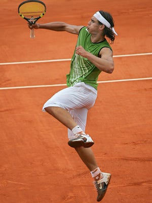 In a file photo from 2005, Rafael Nadal celebrates winning a point against Argentinian Mariano Puerta during their men's final match at the French Open.