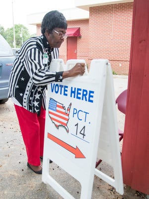 Poll worker Annie Hunter sets up a sign before the polls open on Nov. 8, 2016, at the Fricker Center on Election Day in Pensacola.
