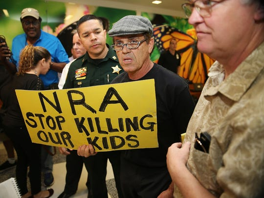 A protester holds a sign that reads, 'NRA Stop Killing Our Kids', outside the court-room where Nikolas Cruz, 19, was having a bond hearing.