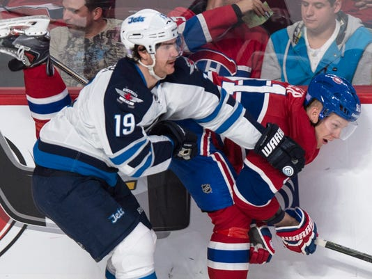 Montreal Canadiens' Lars Eller is checked by Winnipeg Jets' Jim Slater, left, during the first period of an NHL hockey game Tuesday, Nov. 11, 2014, in Montreal. (AP Photo/The Canadian Press, Paul Chiasson)