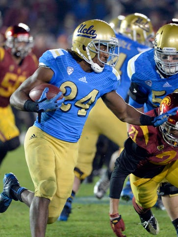 UCLA running back Paul Perkins (24) deflects USC safety