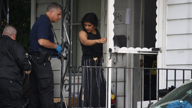 Investigators enter the house in Pleasant Ridge where three people were found dead after apparent carbon monoxide poisoning.