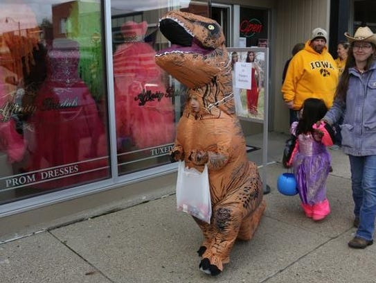 A dinosaur goes door-to-door while trick-or-treating