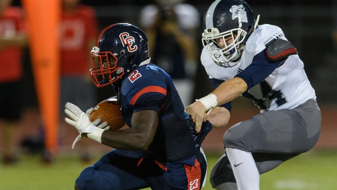 Pinnacle's Kyle Carriker (#44) tries to bring down Centennial's Zidane Thomas (#2) by the jersey in the second quarter of their high school football game on Thursday, Sept. 14, 2017, at Centennial High School in Peoria, Ariz.