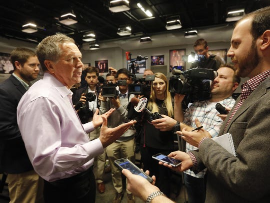 Kasich talks with reporters after speaking at a campaign stop on Dec. 10.