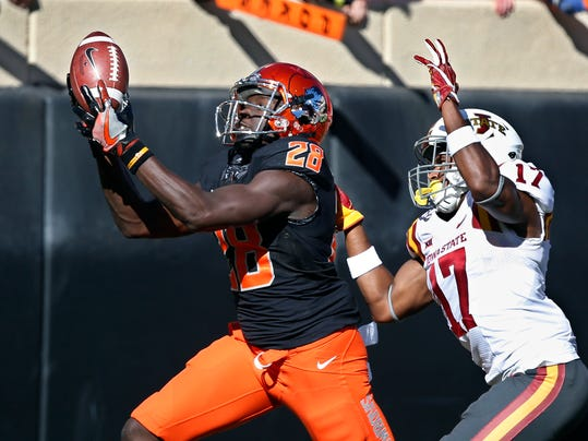 FILE - In this Oct. 8, 2016, file photo, Oklahoma State wide receiver James Washington (28) catches a pass in front of Iowa State defensive back Jomal Wiltz (17) in the second quarter of an NCAA college football game in Stillwater, Okla. For the second straight year, No. 11 Oklahoma State heads into its regular season finale against its intra-state rivals, No. 7 Oklahoma, with a chance to claim the Big 12 title.  (AP Photo/Sue Ogrocki, File)