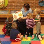 Children gather around Carol Stocksdale as she reads about what hatches from eggs at the Joseph Moore Museum on the Earlham College campus.