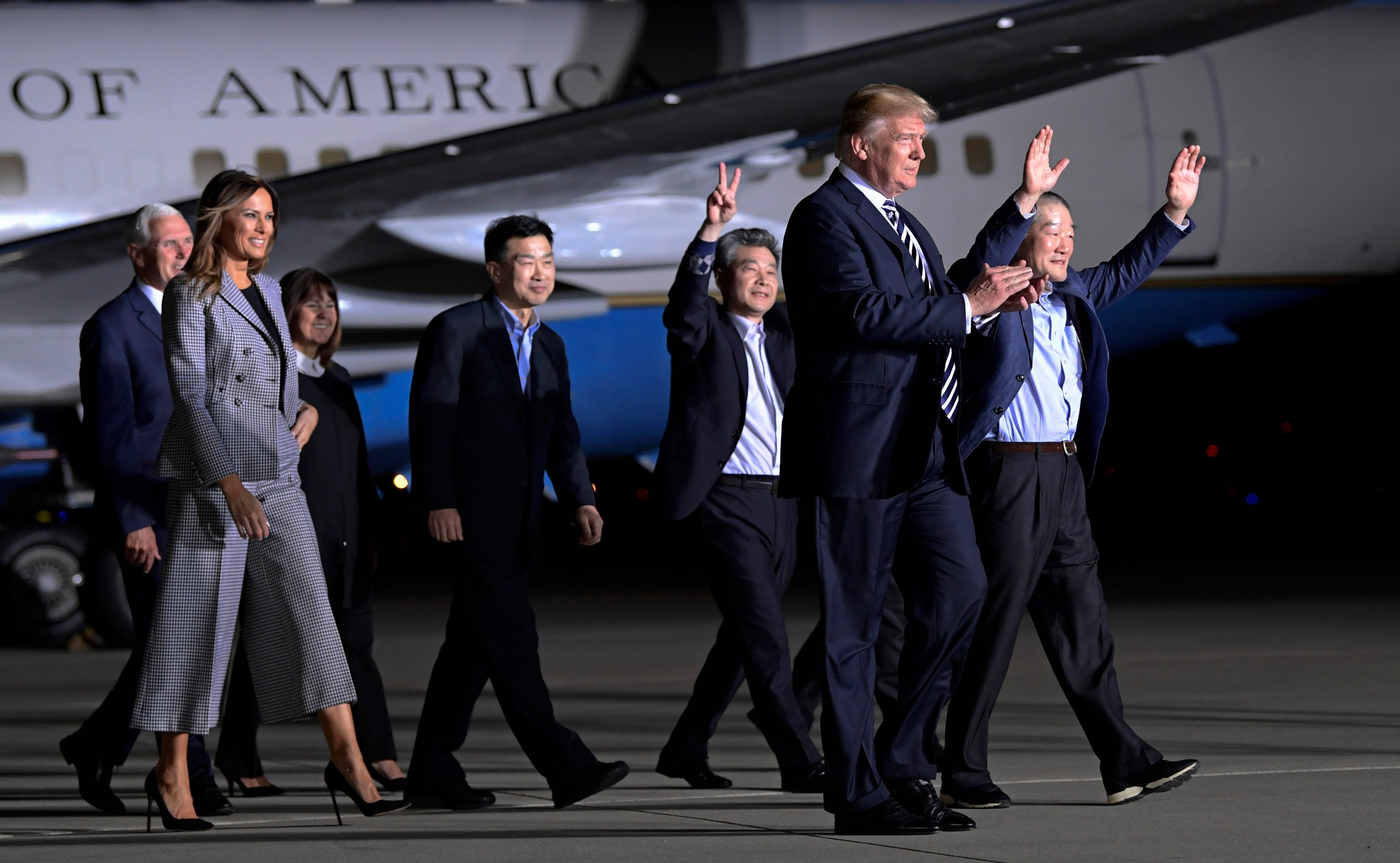 President Donald Trump walks with Tony Kim, fourth