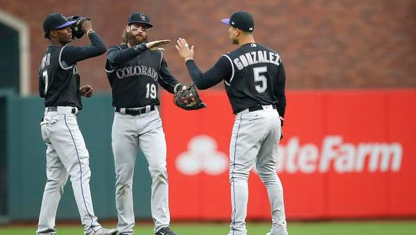 Colorado Rockies left fielder Raimel Tapia (7), center fielder Charlie Blackmon (19) and right fielder Carlos Gonzalez (5) congratulate each other after a 4-3 victory against the San Francisco Giants in a baseball game, Sunday, April 16, 2017, in San Francisco. (AP Photo/Tony Avelar)