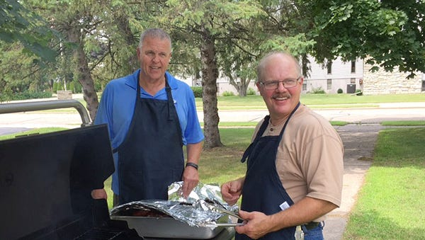 Scott Schiesser, left, and Dennis Hall were on the grill Thursday when The Neighborhood Table served its 250,000th meal.