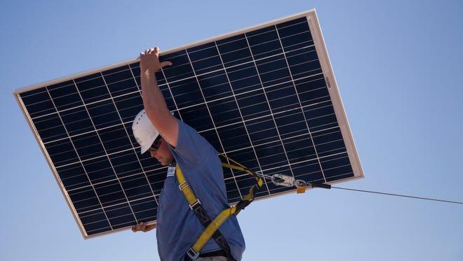 Harmon Solar worker Justin Sullivan installs solar panels on a Buckeye home in 2013.