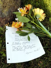 Flowers and condolences handwritten on notebook paper lie at the base of a tree outside Essex Elementary School days after a shooting in 2006.