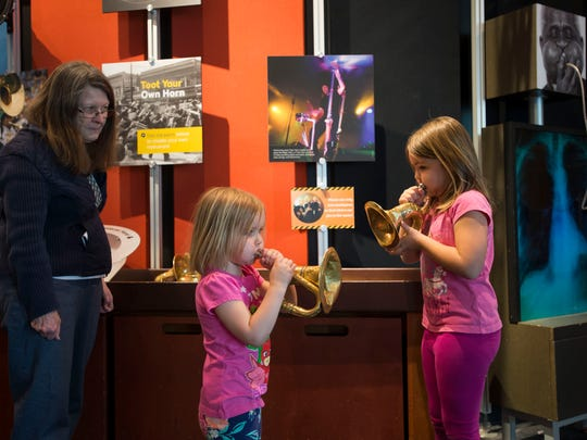 Paige, 3, and sister Elena Gliva, 6, play at an exhibit