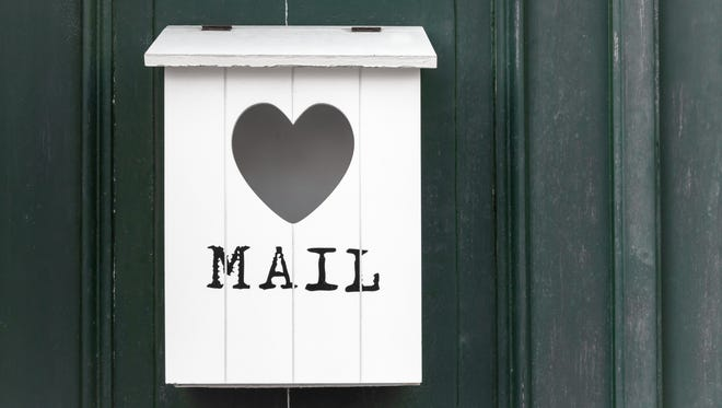 White vintage wooden mailbox with empty heart.
