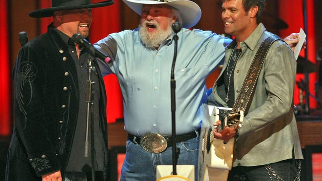 Eddie Montgomery, left, and Troy Gentry, right, celebrate with Charlie Daniels who announced that they are the next Grand Ole Opry members on stage at Grand Ole Opry in Nashville, Tenn., Tuesday, May 26, 2009.