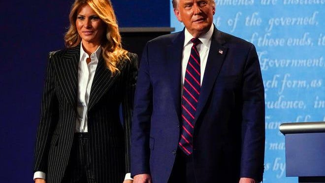 President Donald Trump stands on the stage with First Lady Melania Trump after the first presidential debate with Democratic presidential candidate Joe Biden.