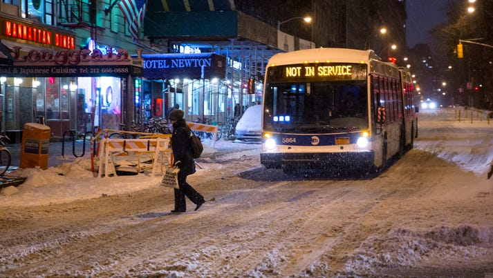 A person crosses a snow-covered Broadway in the Upper