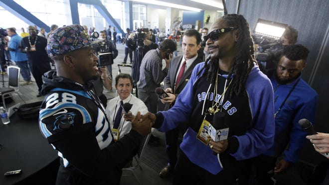 Recording artist Snoop Dogg, right, shakes hands with Carolina Panthers running back Jonathan Stewart (28) during a press conference in preparation for the Super Bowl 50 football game Thursday Feb. 4, 2016 in San Jose, Calif. (AP Photo/Marcio Jose Sanchez)