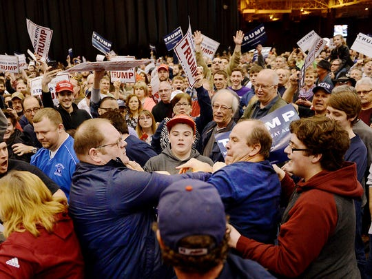 A protester, center left, and a Trump supporter, center right, scuffle during a rally for Republican presidential candidate Donald Trump Saturday, March, 12, 2016, held at the I-X Arena in Cleveland, Ohio.