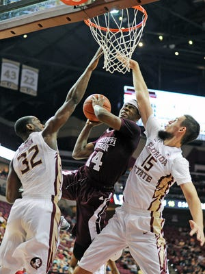 Mississippi State guard Malik Newman (14) is fouled by two Florida State players during their game on Wednesday. Newman left the game in the second half with an injury.