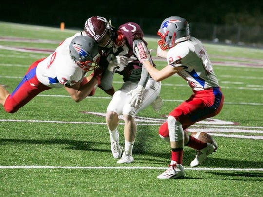 Ty Snelson (39) and William Shelton (22) team up on a tackle and knock the ball loose from an Owen ball carrier.