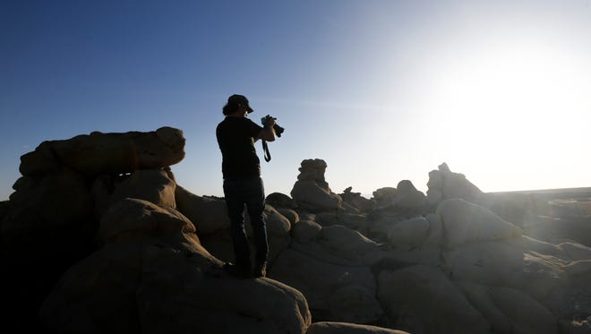 Coby Greenberg, second unit director of Cosmos Production, frames a shot Monday during filming in the Bisti/De-Na-Zin Wilderness area south of Farmington.