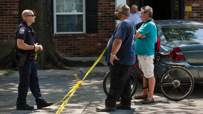 Officer Hambler talks to residents waiting to be allowed back into their apartments after the area was roped off for a crime scene investigation on Thursday afternoon.