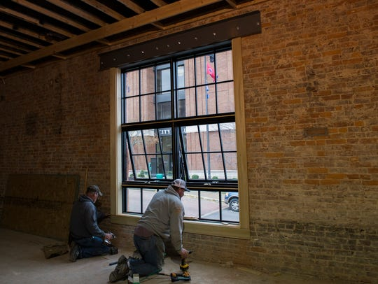 Workers install new windows inside 103 Strawberry Alley,