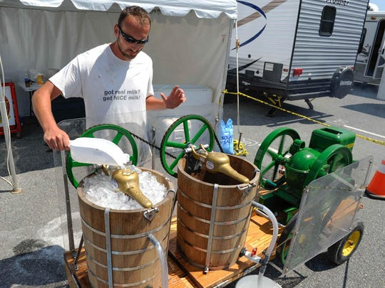 Bob Miller with Nice Farms Creamery in American Corner, Md., mixes their home made ice cream with their 1944 John Deere Model E at the Delaware State Fair in Harrington.