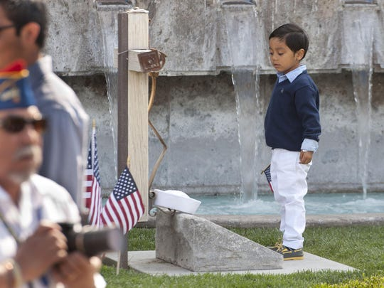 A boy stands at the gravesite of Cesar Chavez before the U.S. Navy ceremony recognizing Cesar Chavez with graveside honors in the Memorial Garden of the Cesar E. Chavez National Monument in Keene on April 23, 2015. Chavez served in the Navy from 1946 to 1948.