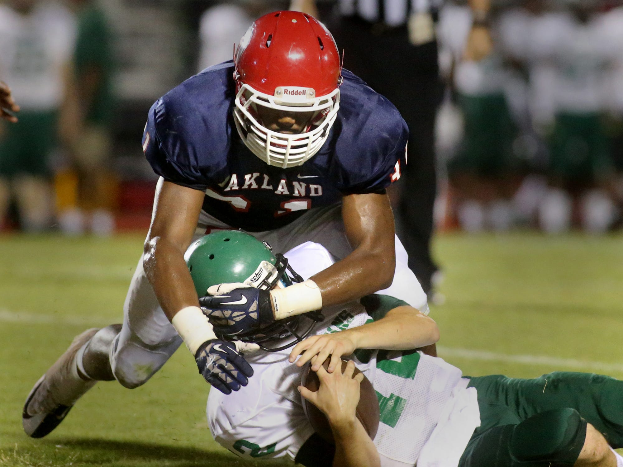 Oakland's Josh Smith takes down White Station quarterback Burk Williams in the first half of the gameagainst White Station at Oakland, on Friday, August 2, 2014.