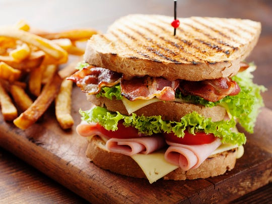 close up of fresh sandwich with ham, bacon,tomatoes,cheese and lettuce