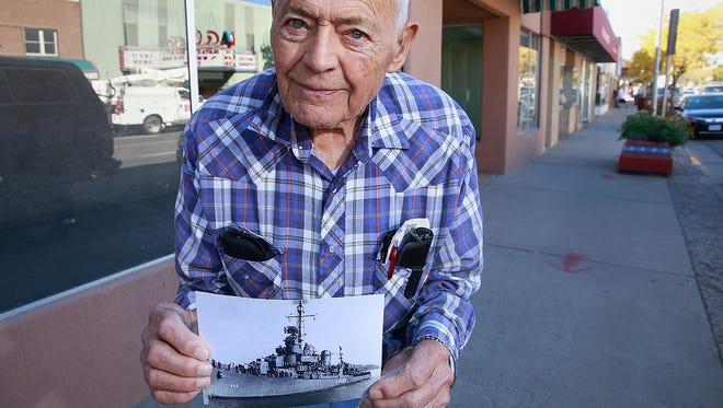 Martin Johnson, a 92-year-old World War II veteran, on Oct. 20 holds a picture of the ship he served on during the war while standing on Main Street in Farmington.