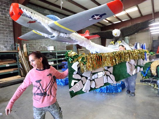 Volunteers Robin Kobren, left, and Gina Chacon on Tuesday carry parts of a float onto a trailer in a warehouse for shipment to the staging area along Montana Avenue for the 2017 FirstLight Federal Credit Sun Bowl Parade. Behind them is the FirstLight float, which will carry a group of World War II veterans being honored as grand marshals.