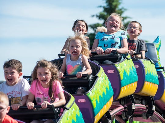 Kids laugh as they ride the Dragon Wagon ride Thursday,