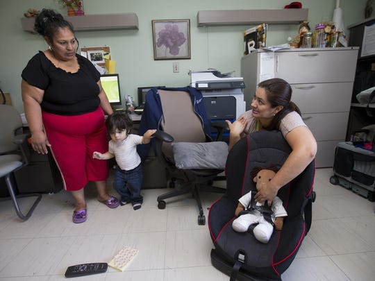 Sandra Lopez-Gascar, left, and her 2-year-old son, Esdres, listen to Maricopa County Department of Public Health educator Monica Falcon talk about car-seat safety during a Children are Priceless Passengers class at Banner Desert Medical Center in Mesa in June.