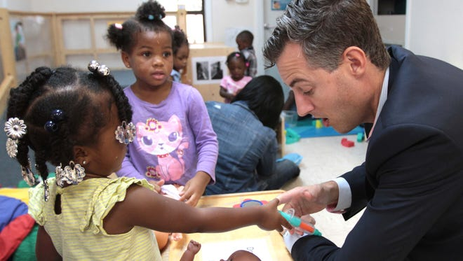 John White, Louisiana superintendent of education, with Danyae Justin, left, and Ameeiah Moses, center, as he visits the Early Head Start Center in West Monroe on Friday.