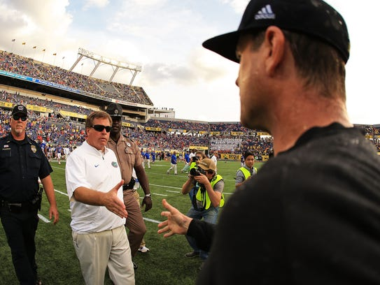 Jim McElwain of the Florida Gators and Jim Harbaugh of the Michigan Wolverines shake hands after the Buffalo Wild Wings Citrus Bowl game Jan. 1, 2016 in Orlando, Fla.