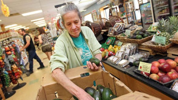 Robin Lindsay, a Newark Natural Foods Co-op produce manager, stocks avocados.