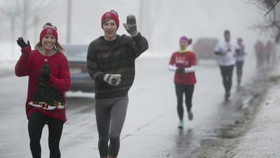 Morgan Irish of Marshfield, left, and Max Tibbett of Marshfield, right, wave as they participate in last year's Hot Chocolate Run in Marshfield Dec. 13, 2014.