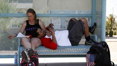Jimi Saindon and Matthew Pride, both of Phoenix, rest at the bus stop near Third Street and McDowell Road in Phoenix on June 12, 2016. Saindon and Pride said they were waiting for the nearby Burton Barr Central Library to open so they could escape the heat.