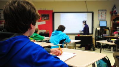 A Lafayette Parish middle school student listens as a teacher shows a lesson. The state has granted the district waivers regarding class sizes.
